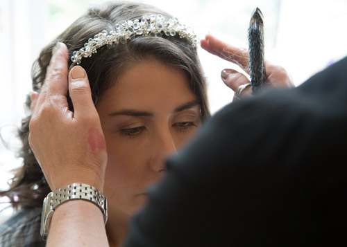 hair stylist placing brides tiara in her hair