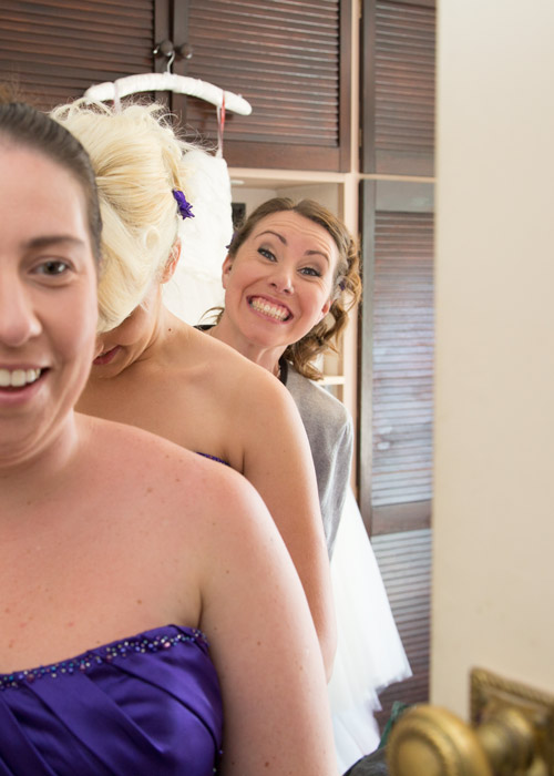 bridesmaid pulling a face while fastening up bridesmaid dresses