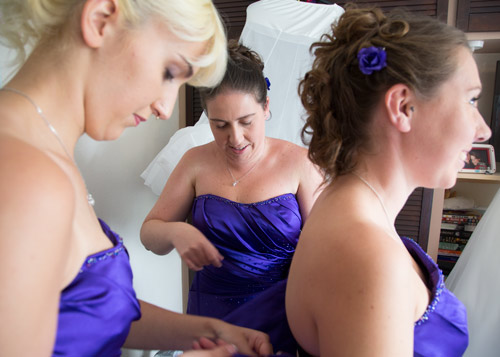 bridesmaids helping each other fasten their dresses