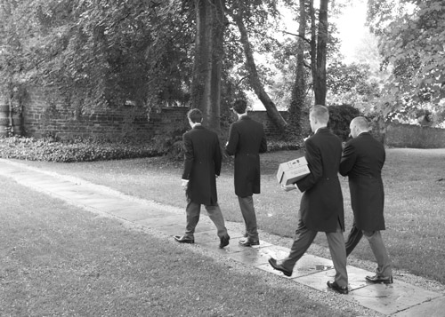 Groom and groomsmen walking to aston church with corsges
