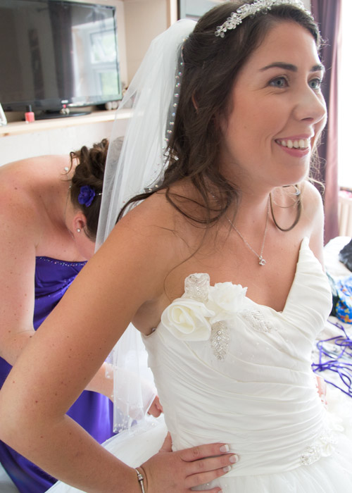 Bridesmaid fastening the wedding dress with a smiling bride