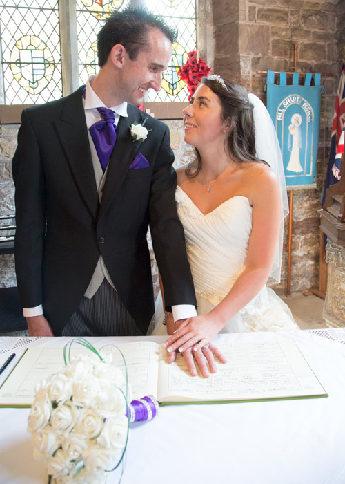 bride and groom looking at each other with their hands on the register at aston church sheffield