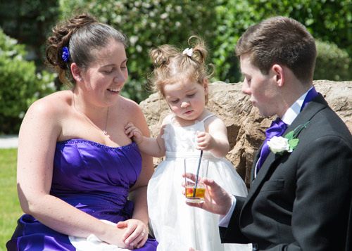 bridesmaid groomsman and flowergirl sitting on a bench outside aston hall hotel