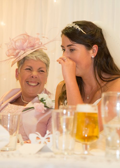 bride and mother of the groom laughing at top table during speeches