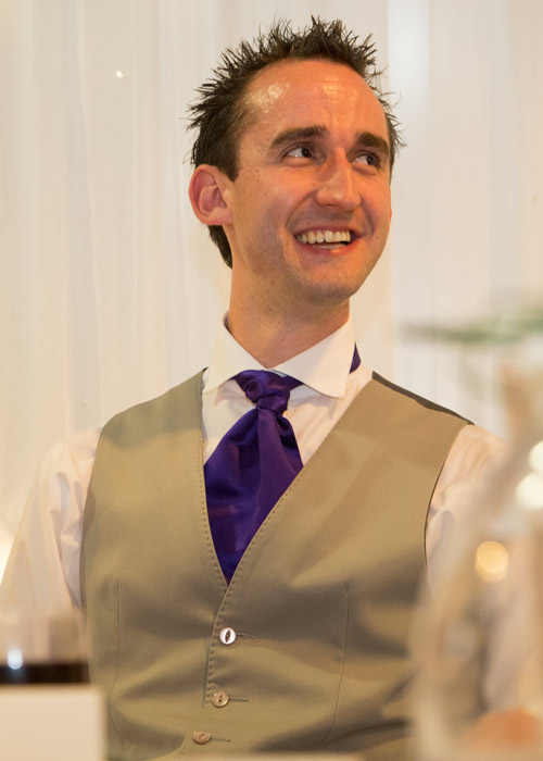 groom in grey waistcoat and purple cravat in front of twinkle backdrop