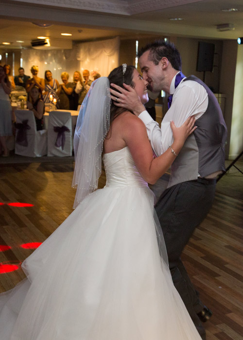 Bride and groom kissing on the dancefloor with guests in the background