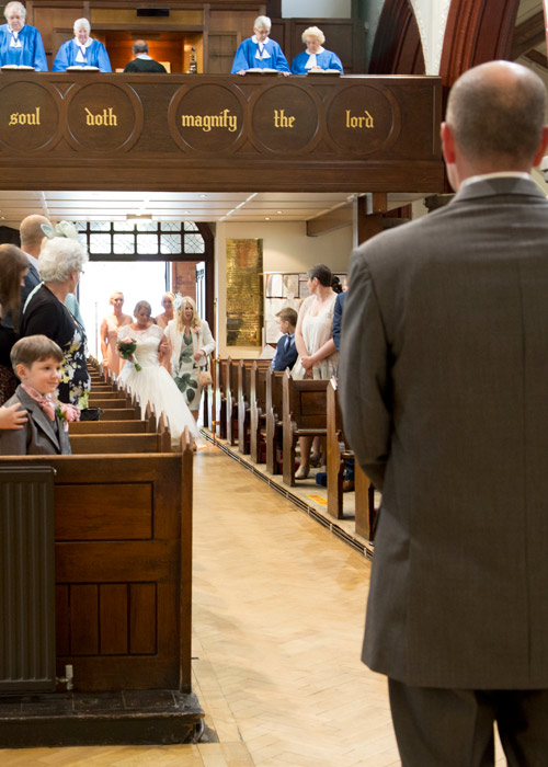 bride walking dwon the aisle with wedding party in monk bretton church barnlsey