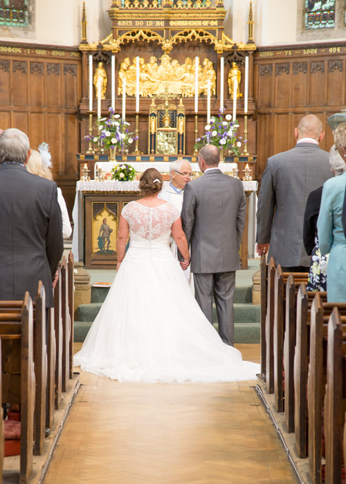 bride and groom at the bottom of the aisle during wedding ceremony monk bretton church barnsley