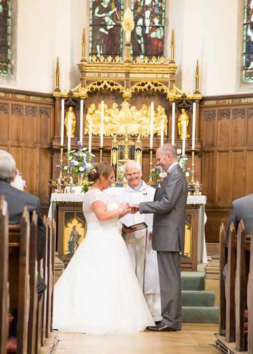bride and groom exchanging rings in monk bretton church laughing at the altar