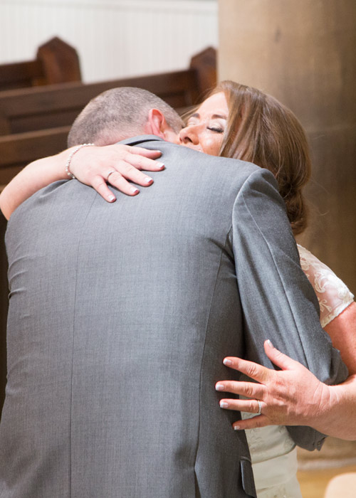 bride and groom hug in monk bretton church during wedding ceremony barnsley