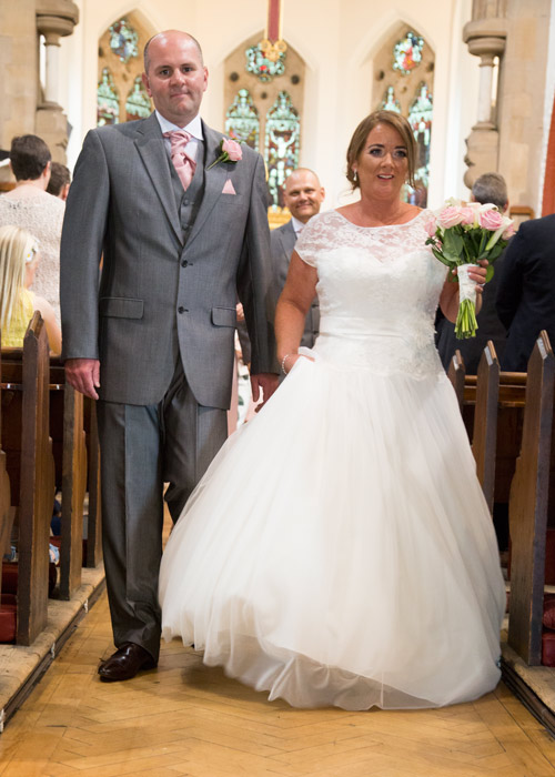 bride and groom walking up the aisle of monk bretton church barnsley