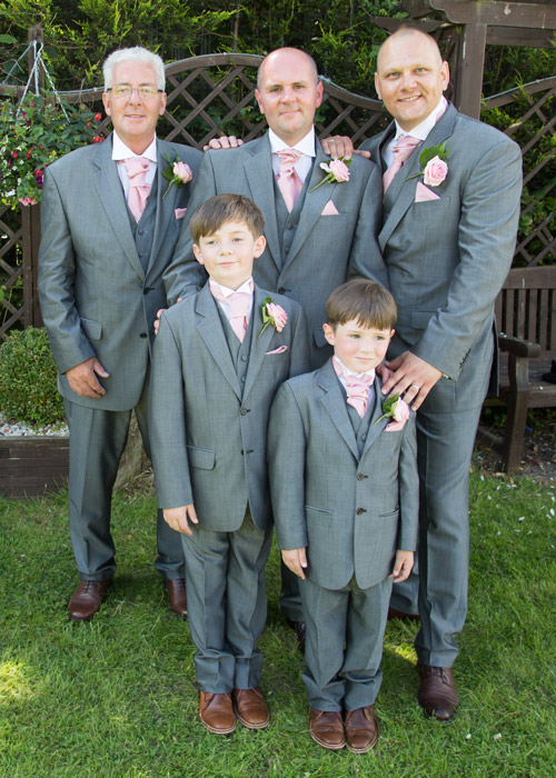 groom with groomsmen and sons in matching grey suits brown shoes and pink corsages