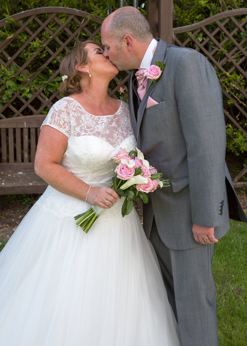 barnsley wedding photography bride and groom kiss holding pink and white bouquet
