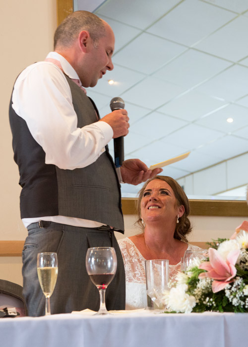 groom giving speech in front of mirror with bride smiling up at him