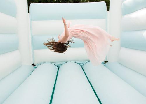 young bridesmaid doing a flip on a bouncy castle fairway barnsley