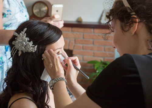 bride with makeup artist on the morning of the wedding