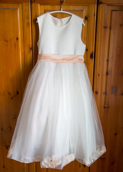 flower girls dress hanging on wardrobe door before it's worn