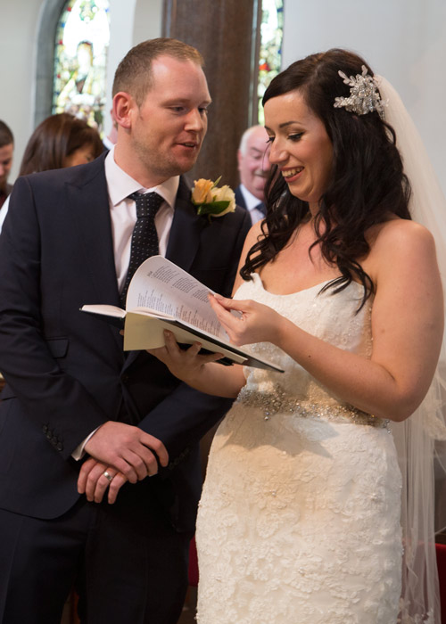 bride and groom reading order of service in st edwards church racecommon road