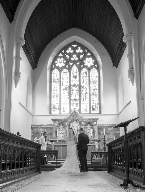 bride and groom in front of altar in st. edwards church barnsley wedding photography