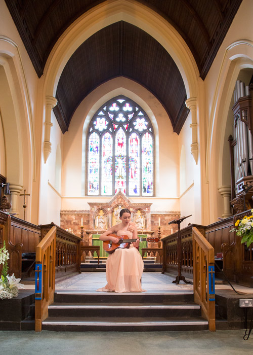 bridesmaid performing acoustic song with guitar during register signing st.edwards church barnsley