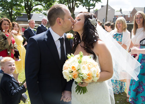 bride and groom kiss with peach and white bouquet