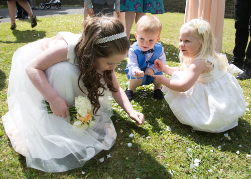 children collecting confetti in church grounds