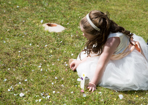 flowergirl collecting confetti from grass