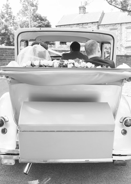 black and white bride and groom in wedding car with open top