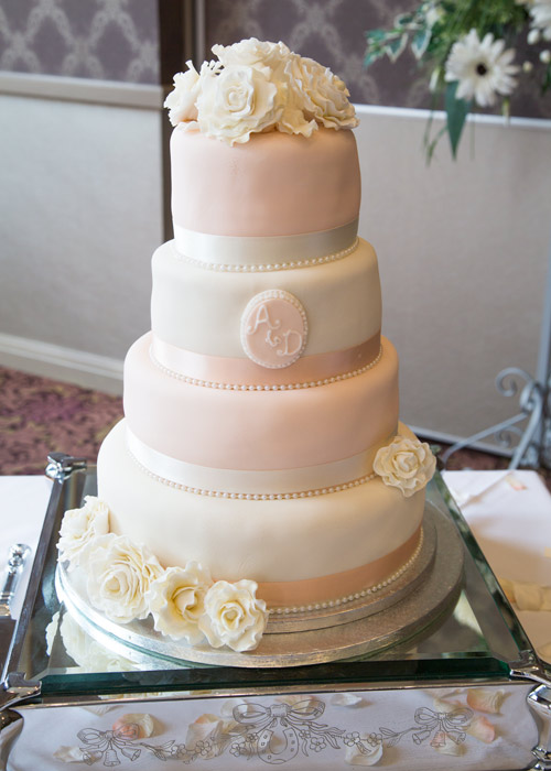 peach wedding cake with white flowers and lettering