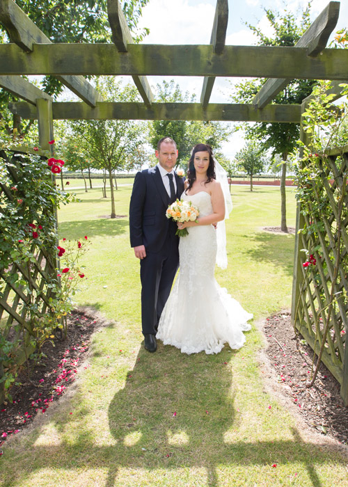 bride and groom under flower arch in burntwood court hotel photographer