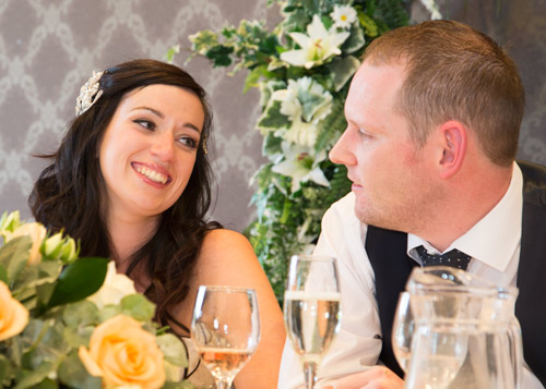 bride and groom at the top table smiling burntwood court hotel photography
