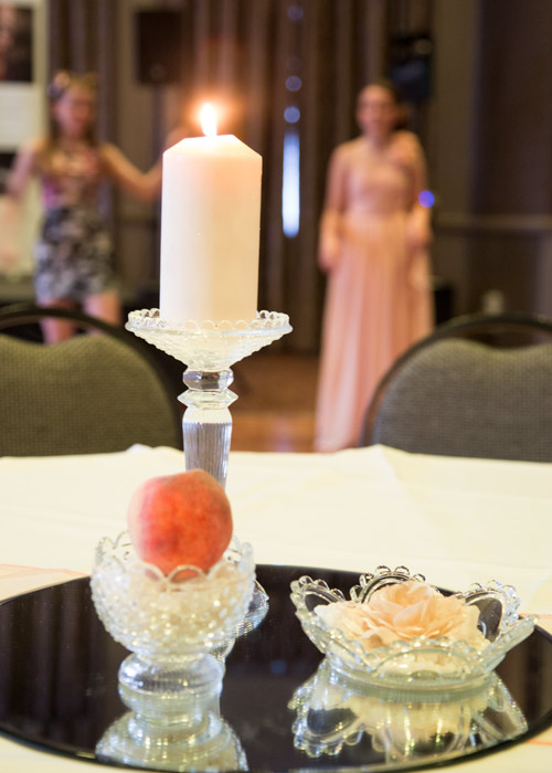 peach wedding theme with lit candle and flower burntwood court hotel
