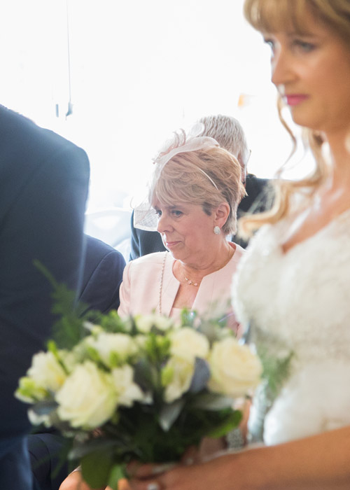 mother of the groom watching the wedding ceremony in dusky pink