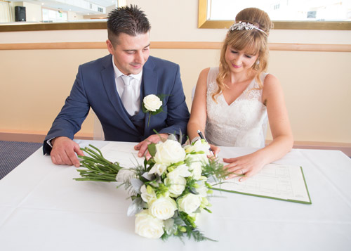bride and groom signing register after the wedding ceremony