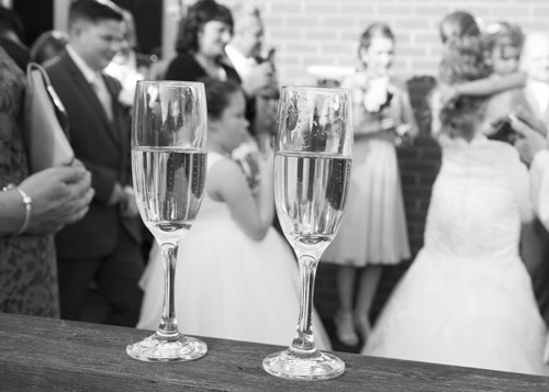 two champaggne glasses in front of wedding guests black and white