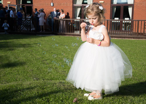 flowergirl blowinng bubbles in the bluebell banqueting suite barnsley garden