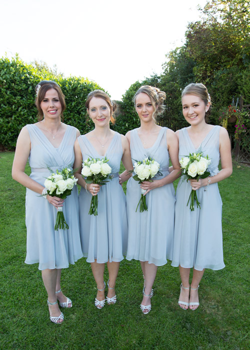 bridesmaids with silver dresses and white flowers