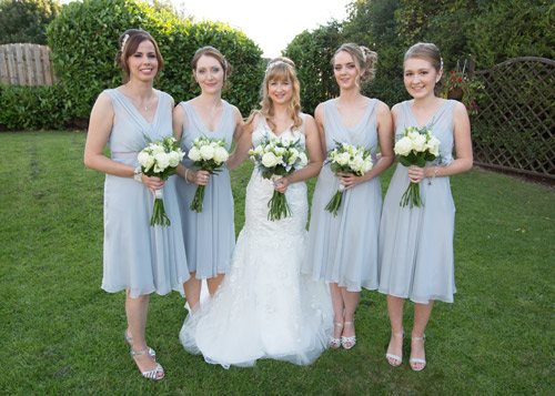 bride with bridesmaids in silver dresses and white bouquets