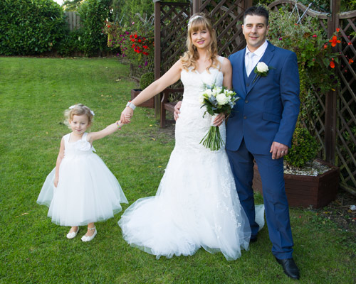 bride and groom with daughter in the garden at fairway pub barnsley