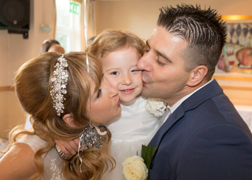 bride and groom kissing daughter on their wedding day with balloon