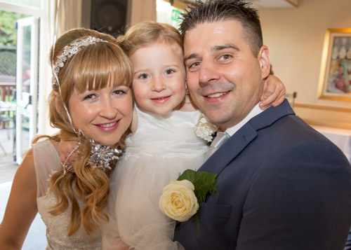 bride and groom with daughter on their wedding day fairway wedding barnsley