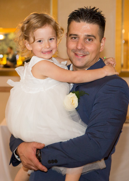 groom in blue suit holding young flower girl