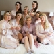 bridesmaids with vintage hairstyles and pink robes on double bed