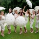 bridesmaids in bespoke dresses dancing with lace umberellas