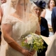 bride with face coverd by veil walking down the aisle