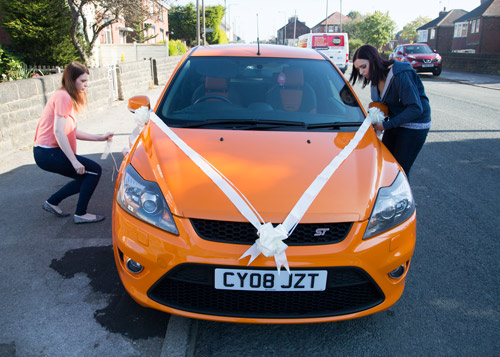 bride and bridesmaid decorating orange wedding car