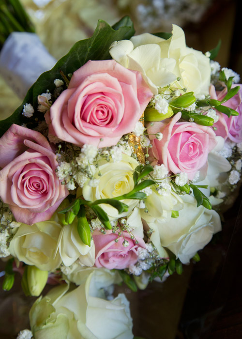 white pink and green bouquet with babys breath and golden pin badge