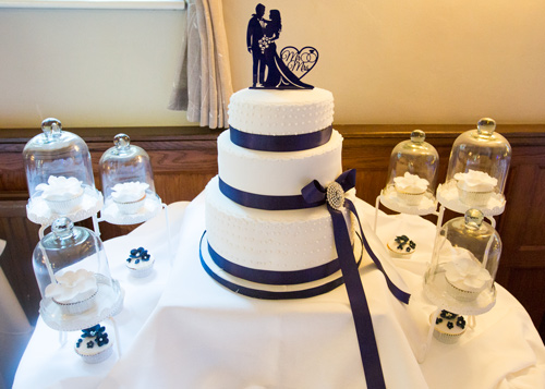 blue and white wedding cake with cased cupcakes