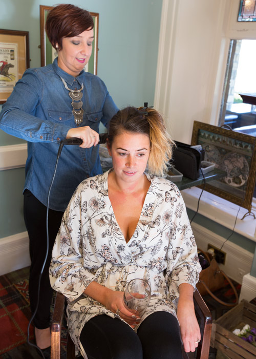 bride with hairdresser on the morning of the wedding