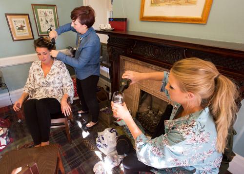 bride and bridesmaid pouring drinks in matching dressing gowns
